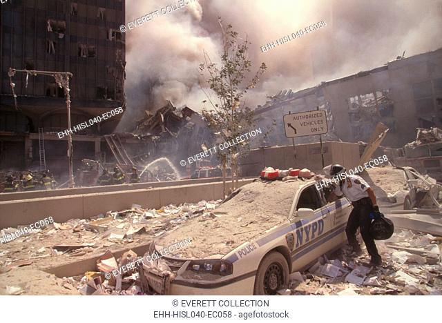 Policeman reaching into a debris covered police car after 9-11 terrorist attack in NYC. At left is still standing WTC 6. At right is the destroyed North...