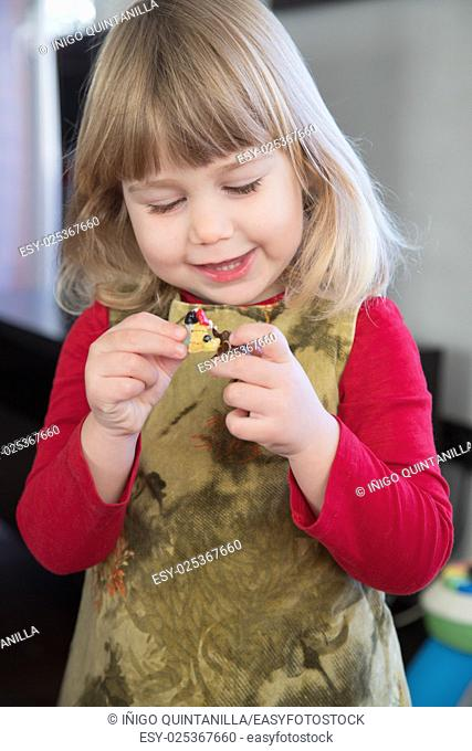 three years old little girl child blonde bang hair with red shirt green dress playing and talking to little dolls in her hands
