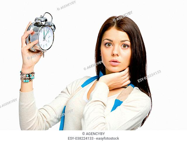 Amazed girl with alarm clock wearing colored scarf and beige pullover, isolated on white