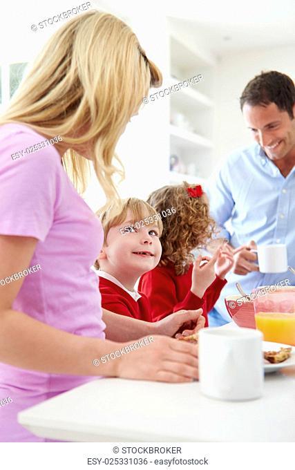Family Having Breakfast In Kitchen Before School