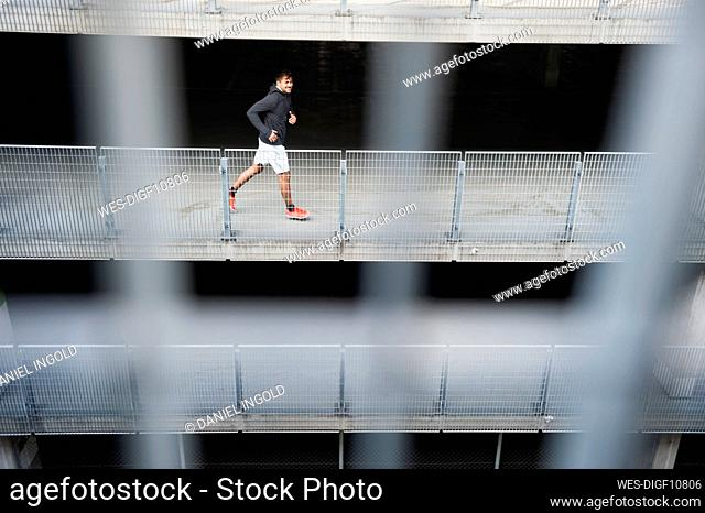 Young man running in a car park