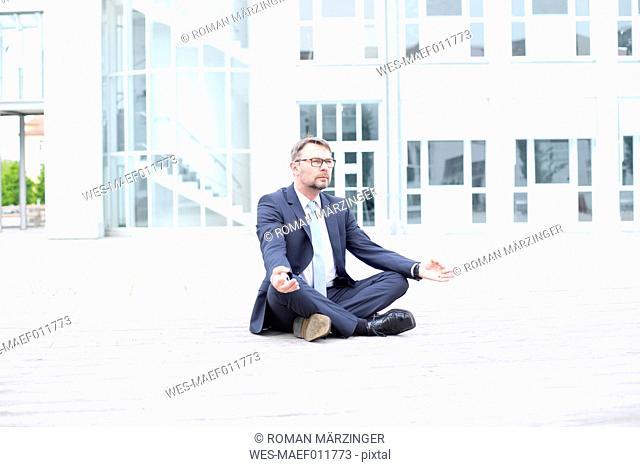 Businessman sitting outdoors meditating