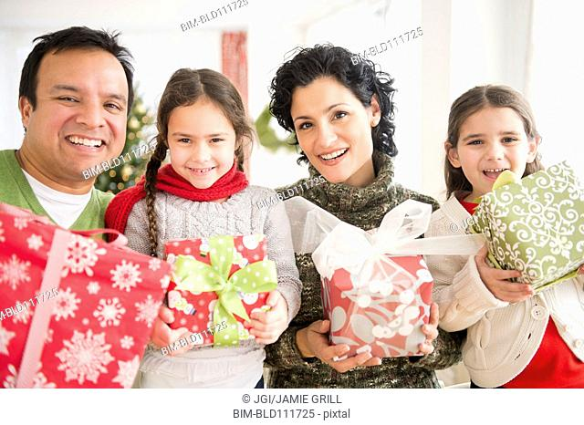 Family holding Christmas presents