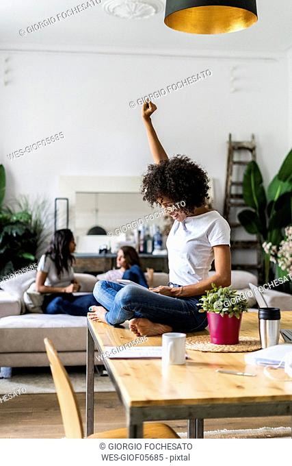 Cheering woman using tablet on table at home with friends in background
