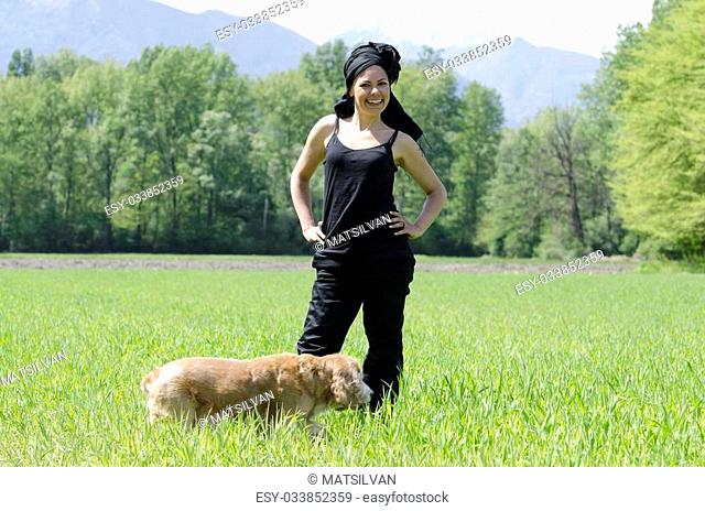 Happy woman standing up on a green field with her dog
