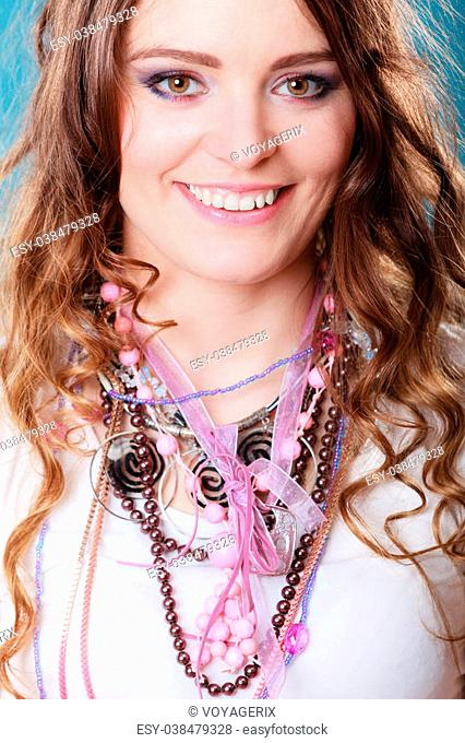 Happy pretty young woman wearing many plenty of jewelry necklaces beads. Portrait of gorgeous fashion girl in studio on blue
