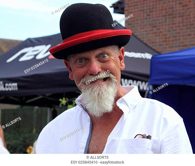 An englishman with a white beard wearing a funny hat