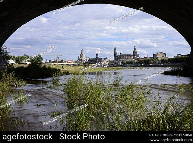09 July 2020, Saxony, Dresden: View through an arch of the Marienbrücke bridge to the historical old town scenery at the Elbe with the Frauenkirche (l-r)
