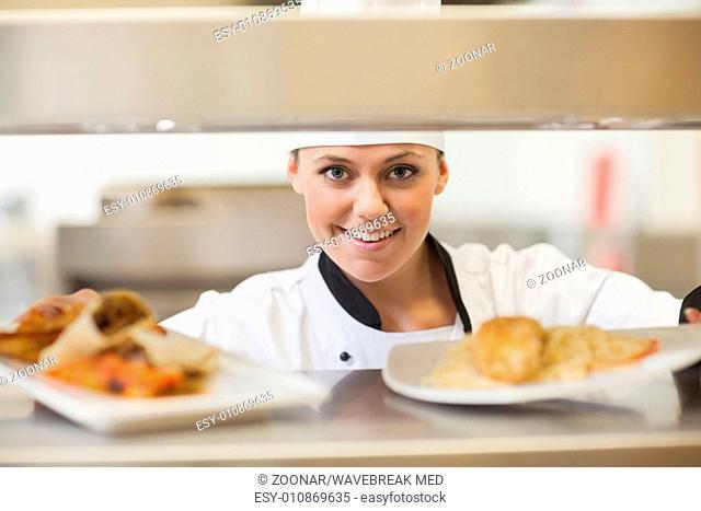 Chef handing dinner plates through order station