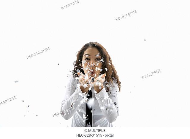 Portrait playful businesswoman blowing confetti against white background