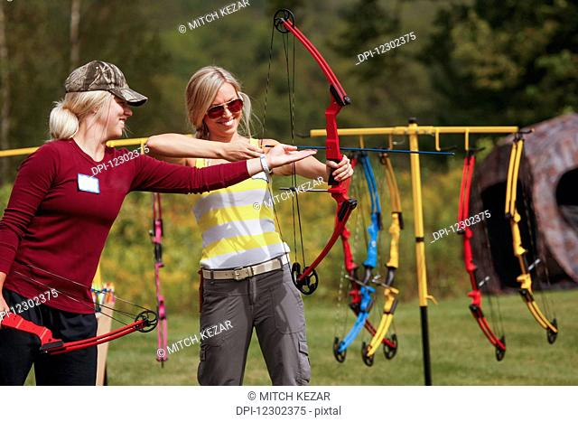 Woman Instructs Younger Woman On How To Shoot A Bow
