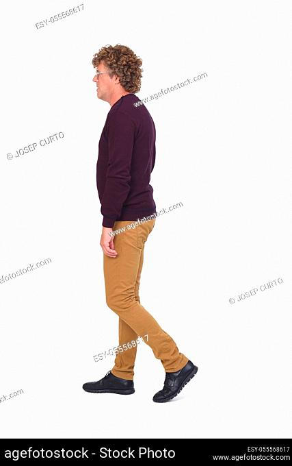 side view of a man with curly hair walking on white background