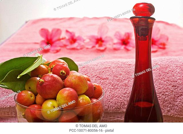 Spa elements, a pink towel, bowl of fruit, glass bottle and line of flowers blurred in background
