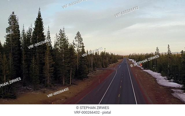 High angle shot of cars driving on road through forest
