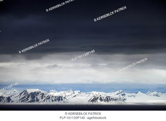 Black rain clouds over snow covered mountains along Isfjorden, second longest fjord at Spitsbergen / Svalbard