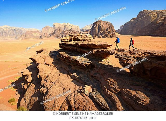 Couple hiking at Rock Arch, Al Borg Alsagheer, Wadi Rum, Jordan