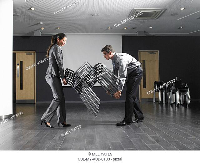 Man and woman moving stack of chairs in empty presentation room