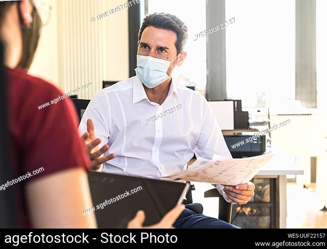 Business people wearing face mask having discussion in meeting while sitting at office