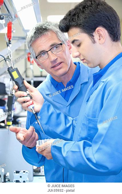 Supervisor training technician to use electric screwdriver to assemble machine part on production line in manufacturing plant