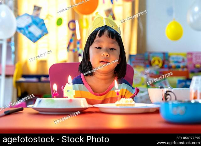 Asian girl kid with her birthday cake celebrate alone with family because city lockdown while COVID-19 Pandemic. Celbration and quarantine concept