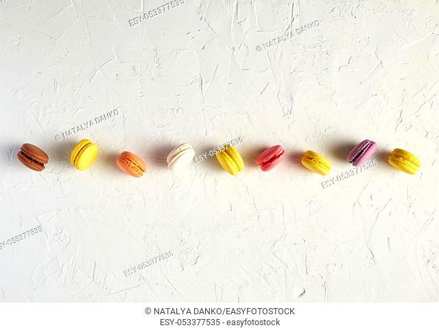 assortment of multi-colored baked round macarons on a white background, flat lay, copy space
