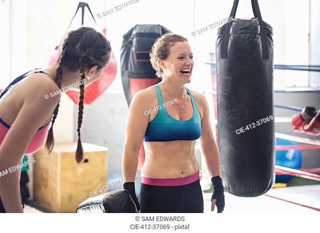 Laughing female boxers next to punching bags in gym