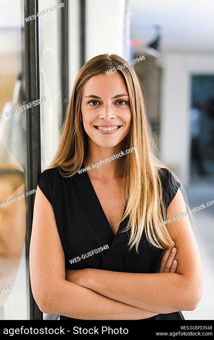 Young businesswoman standing in office, with arms crossed