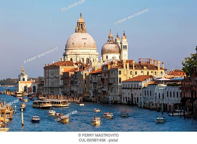 Water taxis and vaporettos on Grand Canal, Renaissance architectural style palace buildings, Santa Maria della Salute basilica, Dorsoduro, Venice, Veneto, Italy
