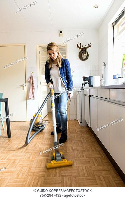 Tilburg, Netherlands. Young caucasian woman dustcleaning the floor of her kitchen