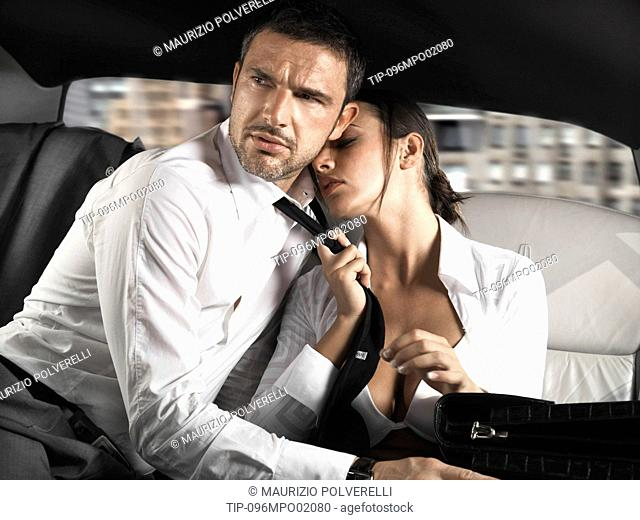 Businessman and businesswoman sitting in the back seat of a limousine, woman pulling man's tie