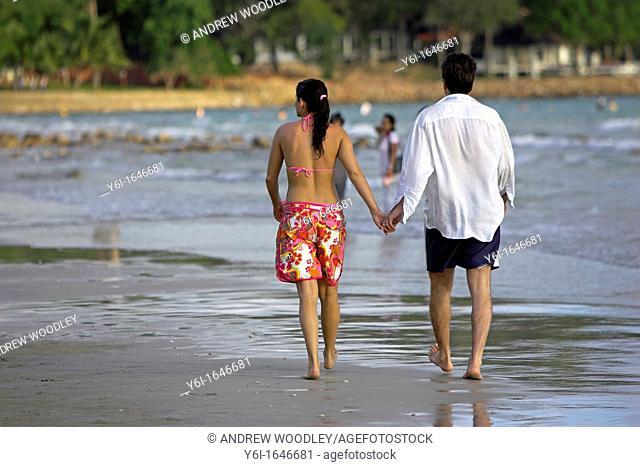 Couple stroll hand in hand on beach Ko Chang Thailand