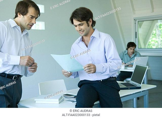 Two businessmen looking at document together in office