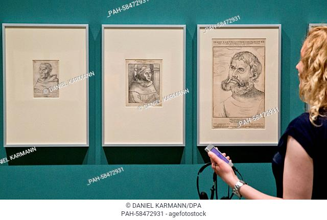 A woman holds a specially made audio guide in her hand as she looks at the copperplate engravings 'Martin Luther als Augustinermoench' (L-R, lit