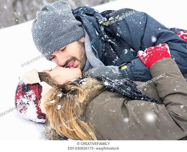 Close up of a couple on a winter day kissing on the snow