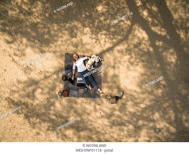Bird's eye view of woman lying on blanket with dog and utensils