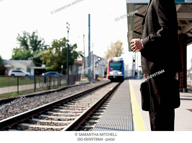 Businessman waiting for approaching train