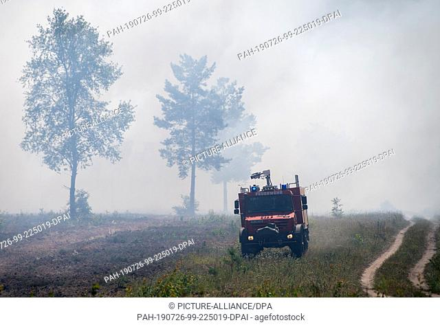 26 July 2019, Brandenburg, Jüterbog: In the event of a forest fire, a fire engine drives over the smoky terrain on a former military training area near Jüterbog