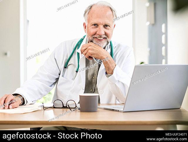 Smiling male medical professional at desk