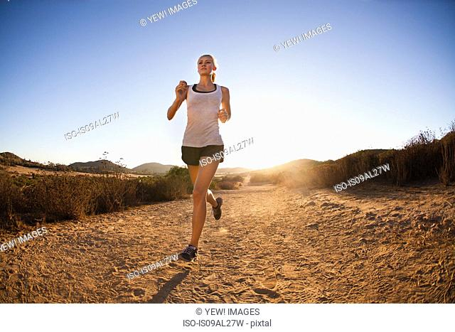Young woman jogging on sunlit path, Poway, CA, USA