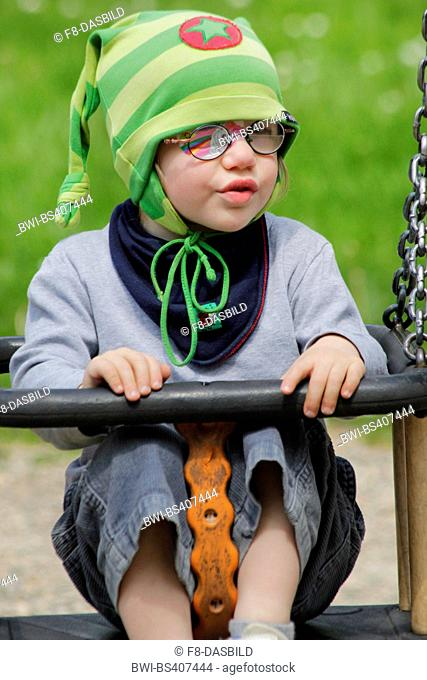 little girl with eye patch sitting amused in a swing, Germany