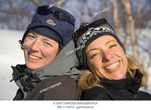 Two woman in a cheerful mood sitting back to back in the snow, Kiruna, Lapland, North Sweden, Sweden, Europe