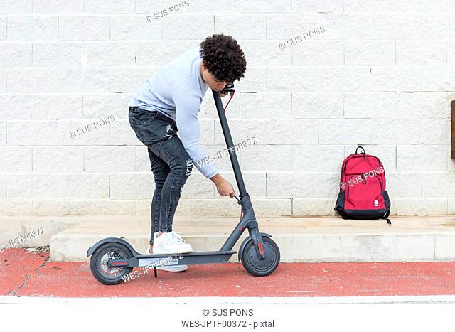 Young man folding e-scooter