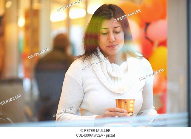 Mature female tourist drinking coffee in cafe window seat, Tokyo, Japan