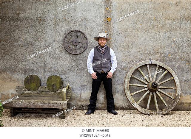 Bearded man wearing Stetson standing with his hands in his pockets outside a barn next to a wooden bench and large wooden carriage wheel