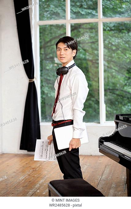 Young man standing next to a grand piano in a rehearsal studio, holding sheet music