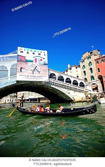 Gondola ride in Grand Canal of Venice with La Biennale exhibition poster on bridge, Italy