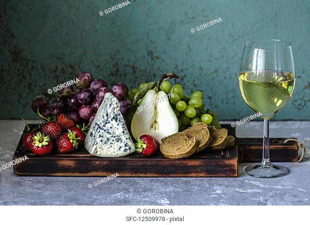 A glass of white wine and snacks for wine