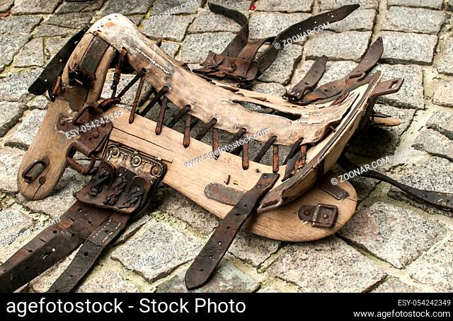 Old vintage horse saddle leather and wooden base frame tree closeup on stone paved ground surface