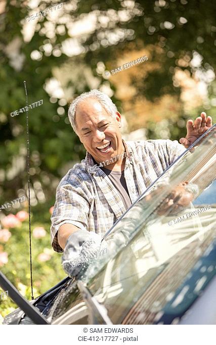 Happy man washing car