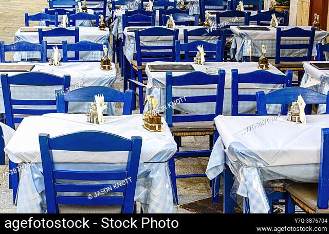 Mesas vacías de una taberna griega y sillas azules